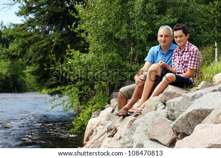 Beautiful shot of father and son sitting on rocks by the river enjoying summer at the cottage.
