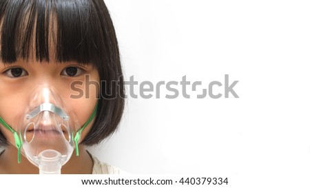 Beautiful sick girl inhalation therapy by the mask of inhaler . Close up image of a cute kid with respiratory problem or asthma with copy space. View of copyspace of sick girl with clear oxygen mask. - stock photo