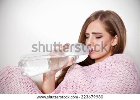 Beautiful sick woman drinking water - stock photo