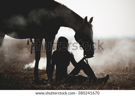 Beautiful silhouette of a girl who sits next to a horse and feed her with his hands against a white background. Woman sitting in the field on a background of smoke, and next to her is her horse - stock photo