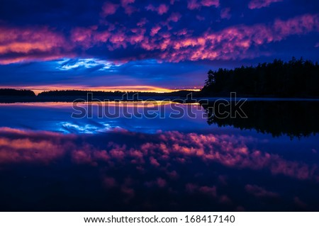 Beautiful silhouette of a sunset in Tofino, British Columbia reflection off the calm cove split in half by a distant island. - stock photo
