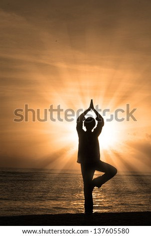 Beautiful silhouette of a woman practicing yoga at beach