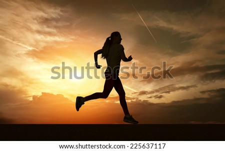 Beautiful silhouette of female running on road under sky with sun light