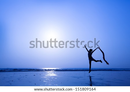 beautiful silhouette of slim woman dancing on the beach - stock photo