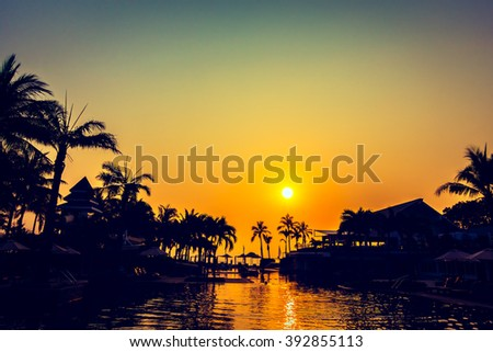 Beautiful Silhouette palm tree with umbrella and chair around luxury swimming pool in hotel resort at sunset time - Vintage Filter and Color boost Up Processing