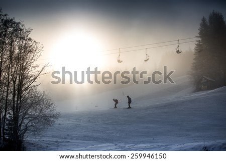 Beautiful silhouette photo of riding skiers and ski lift against bright winter sun - stock photo