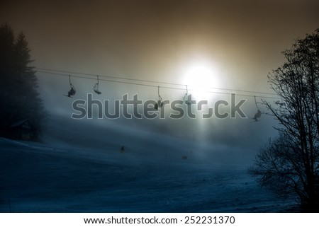 Beautiful silhouette photo of ski lifts shot against bright sun in mountains - stock photo