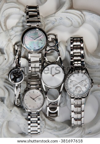 beautiful silver bracelet watches in a vintage background with a beautiful light - stock photo