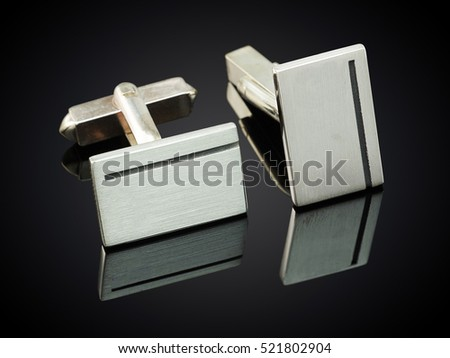 beautiful silver cufflinks on black background.