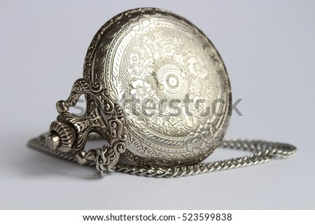 Beautiful silver pocket watch with long chain close-up isolated on a gray background with flower patterns back view