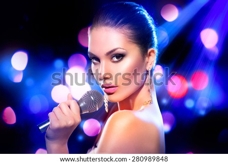 Beautiful Singing Girl. Beauty Glamor fashion Woman with Microphone over Blinking bokeh night background. Glamour Model Singer. Karaoke song. Karaoke party - stock photo