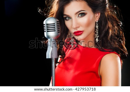 Beautiful Singing Girl. Beauty Woman in red dress with Microphone