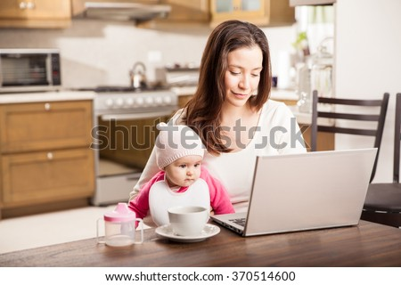 Beautiful single mom working at home on a laptop computer while taking care of her baby girl - stock photo