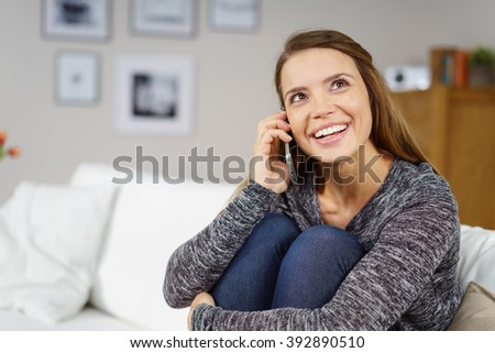 Beautiful single young adult woman in gray sweater holding knees while sitting on white sofa and talking on cell phone indoors - stock photo
