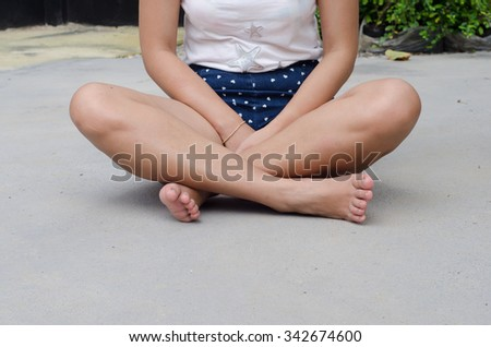 Beautiful sitting woman smooth on a concrete floor - stock photo