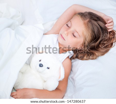 beautiful six year old girl sleeping in the bed with her teddy bear