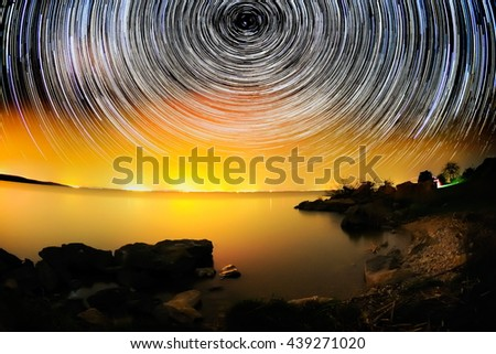 beautiful sky at night with startrails and lake - stock photo