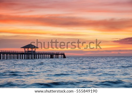 Beautiful sky at sunset with wooden bridge in sea.
