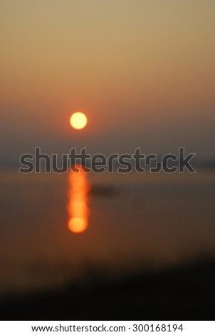 Beautiful sky landscape with sunset over river bank, blur background - stock photo