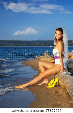 beautiful slavonic bride in body and sun-glasses sitting on trunk. blue sky and sea on backround. - stock photo