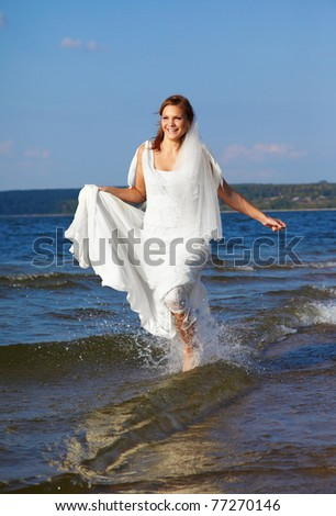 beautiful slavonic bride running in sea waves