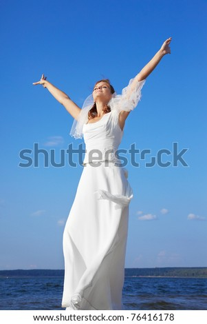 beautiful slavonic bride spreading hands to sun. blue sky and sea on backround. - stock photo