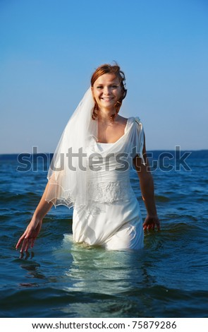 beautiful slavonic bride walking in sea waves - stock photo