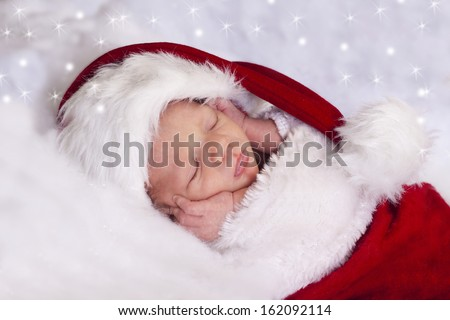Beautiful sleeping baby boy dressed up as Santa Claus.