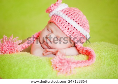 beautiful sleeping baby wearing a striped hat - stock photo