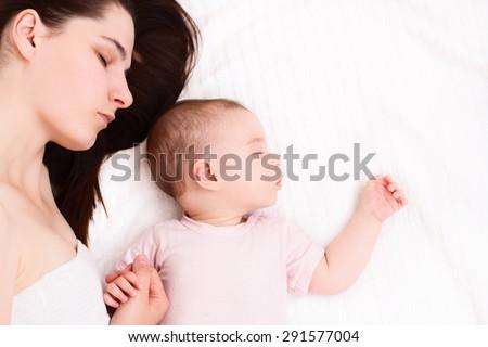 Beautiful sleeping baby with mom on white background - stock photo