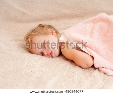 Beautiful sleeping child. Peaceful child lying on a bed in a bright room.