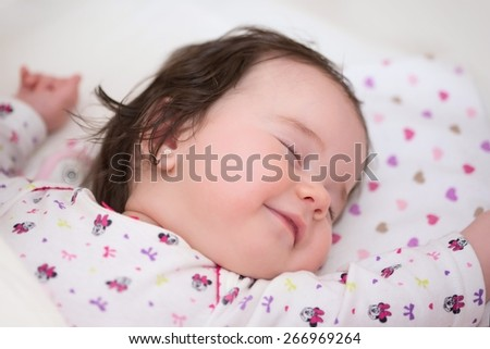 Beautiful, sleeping little girl with a slight smile on his lips - nice dreams - stock photo