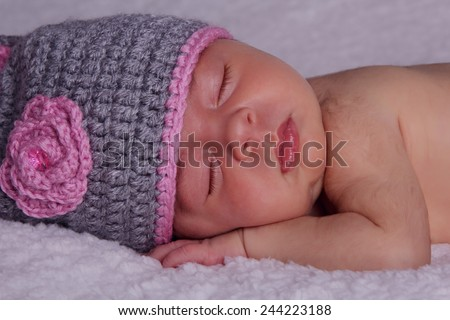 Beautiful sleeping newborn baby in knitted cap under the rug - stock photo