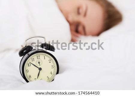 Beautiful sleeping woman with alarm clock. Focus on clock. - stock photo