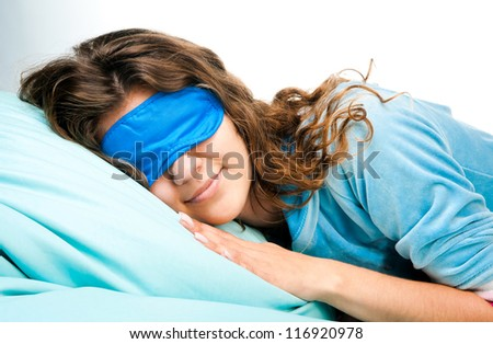 Beautiful sleeping young woman in sleep eye mask on blue furnishing