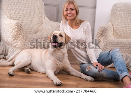 Beautiful  slender blond girl in jeans and beige knitted jacket  sitting on floor  with Labrador Retriever smiling looking at camera