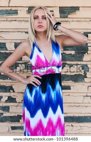 Beautiful slender blonde against a peeling wall - stock photo
