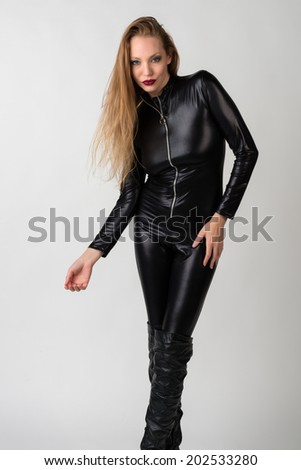 Beautiful slender blonde in a black catsuit - stock photo