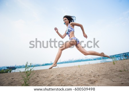 Beautiful slender brunette in a swimsuit running on the beach with a stride