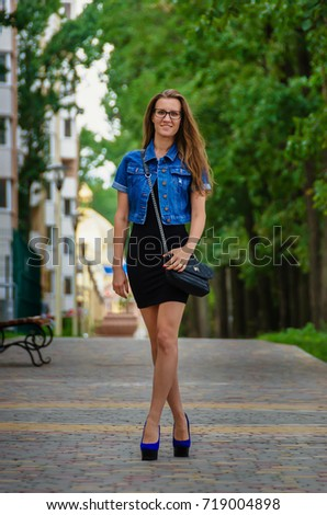 beautiful slender fashion woman in a black dress and denim blue jacket walking along the sidewalk in the park near the house in the summer