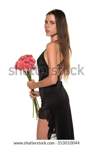 Beautiful slender young brunette with a bouquet of pink flowers - stock photo