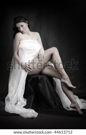 Beautiful slenderness young woman in bridal veil on black background. Low key studio shot. Great for calendar and Valentine advertising. - stock photo