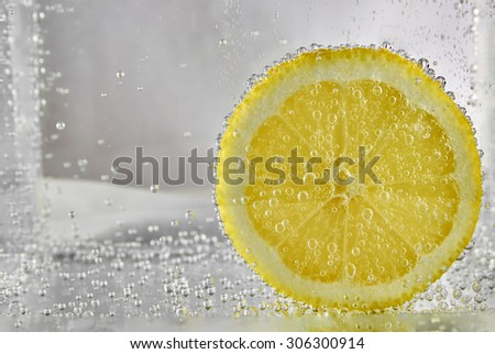 Beautiful slice of lemon in the water with bubbles of gas. design element - stock photo