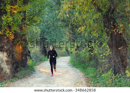 Beautiful slim and fit girl running in nature on sunny autumn day. - stock photo