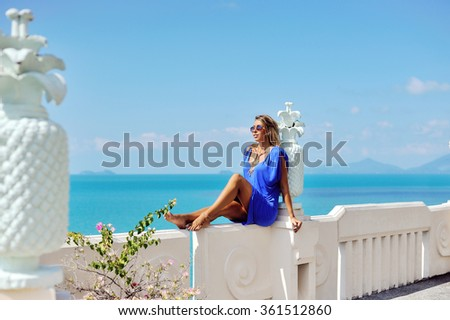Beautiful slim blonde girl model posing in fashion dress by the sea, outdoor portrait