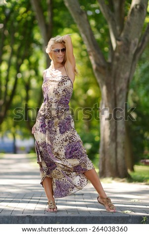 Beautiful slim blonde girl with a beautiful tan in a summer dress developing in the wind in sunglasses walking in the park - stock photo