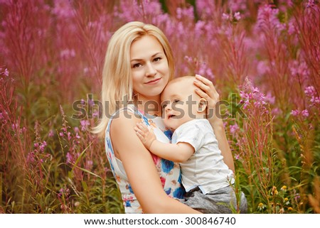 Beautiful slim blonde mom hugs adorable little boy , on the background of grass fireweed in the summer - stock photo