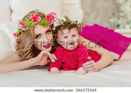 Beautiful slim blonde mom in red dress and a wreath of flowers lying next to the bed with a young daughter and a wreath - stock photo