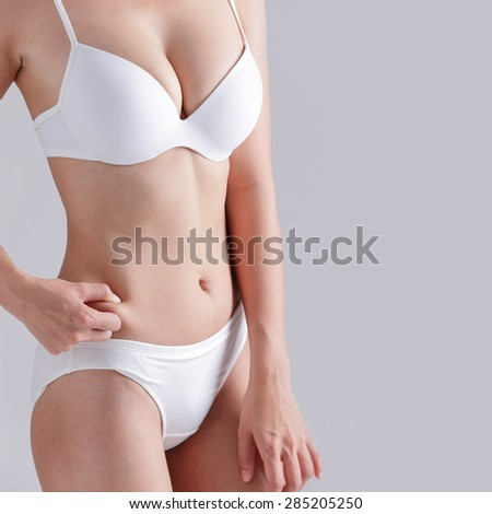 Beautiful slim body of woman and she measuring her stomach isolated on gray background - stock photo