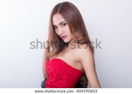 Beautiful slim body of woman in studio, white background, red dress.
